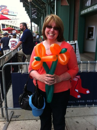 woman standing outside Fenway park with balloon flowers