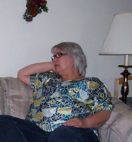 picture of overweight woman sitting on couch in blue and yellow shirt