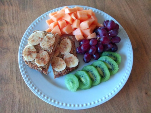 plate of canteloupe, grapes, kiwi, and bananas on toast